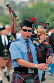 A YOUNG PIPER GIVES IT HIS ALL MARCHING ALONG PRINCES STREET, EDINBURGH. SUNGLASSES,PIPE BAND,SUMMER,TARTAN,KILT,EVENT,PEOPLE,BAGPIPES
