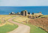 LOOKING DOWN THE ROAD LEADING TO THE IMPRESSIVE RUINS OF DUNNOTTAR CASTLE- DATING FROM THE LATE 14C AND ONE OF THE MOST THEATRICALLY SITUATED CASTLES IN SCOTLAND, SOUTH OF STONEHAVEN, ABERDEENSHIRE. P... SUNNY,CLIFF,BUILDING,DRAMATIC,HERITAGE,COAST,SUMMER,WATER