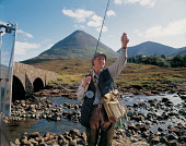 A FISHERMAN ATTENDS TO HIS LINE WHILE FISHING ON THE SLIGACHAN RIVER, RUNNING NORTH FROM THE CUILLIN HILLS TO THE HEAD OF LOCH SLIGACHAN, ISLE OF SKYE. PIC: P.TOMKINS/VisitScotland/SCOTTISH VIEWPOINT... CHARACTER,PEOPLE,AUTUMN,ACTIVITY,FLY,SPORT,WATER