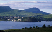 LOOKING ACROSS LOCH PORTREE TO THE HOUSES OF PORTREE (THE PRINCIPAL TOWN OF THE ISLAND), WITH THE OLD MAN OF STORR ON THE TROTTERNISH RIDGE VISIBLE BEHIND, SKYE, INNER HEBRIDES. PIC: VisitScotland/SCO... SUMMER,BUILDINGS,FISHING,BOAT,BAY,SUNNY