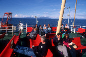 LOOKING OVER PASSENGERS ON THE DECK OF THE CASTLEBAY / OBAN  CALEDONIAN MACBRAYNE FERRY, WITH A VIEW TO THE ISLE OF RHUM (RUM) IN THE DISTANCE, INNER HEBRIDES. PIC: P.TOMKINS/VisitScotland/SCOTTISH VI... WATER,SUNNY,SUMMER,TRANSPORT,ISLAND,PEOPLE