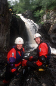 """TWO PEOPLE POSE FOR A PHOTOGRAPH DURING AN AFTERNOON OF """"CANYONING"""" (JUMPING DOWN A WATERFALL) WITH """"VERTICAL DESCENTS"""" AT INCHREE FALLS, ONICH, HIGHLAND.  PIC: P.TOMKINS/VisitScotland/SCOTTISH VIEWPO... PEOPLE,ACTIVITY,EXTREME SPORTS,WATER,WETSUIT,ADVENTURE SPORT,SMILE"""