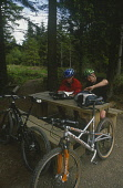 TWO MOUNTAIN BIKERS ENJOY A PICNIC DURING AN AFTERNOON'S CYCLING AT THE PURPOSE BUILT MOUNTAIN BIKING CENTRE IN GLENTRESS FOREST IN THE TWEED VALLEY FOREST PARK, SCOTTISH BORDERS  PIC: P.TOMKINS/Visit...