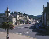 LOOKING ALONG THE MAIN STREET THROUGH THE CENTRE OF PEEBLES- A SMALL TOWN AND RESORT ON THE RIVER TWEED, SCOTTISH BORDERS.  PIC: P.TOMKINS/VisitScotland/SCOTTISH VIEWPOINT Tel: +44 (0) 131 622 7174... SUMMER,SUNNY,HANGING BASKET,LAMPOST,CARS,SHOPS,SHOPPING,2003