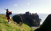 A PIPER IN FULL HIGHLAND DRESS ON THE CLIFF TOP WITH THE IMPRESSIVE RUINS OF DUNNOTTAR CASTLE- DATING FROM THE LATE 14C AND ONE OF THE MOST THEATRICALLY SITUATED CASTLES IN SCOTLAND, BEHIND, SOUTH OF... WATER,SUMMER,SUNNY,COAST,HERITAGE,BUILDING,DRAMATIC,BAGPIPES,TARTAN,KILT,PEOPLE