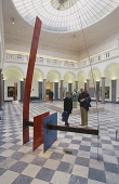TWO VISITORS EXAMINE ONE OF THE WORKS OF ART IN THE SPLENDID MARBLE AND GRANITE CENTRE COURT OF ABERDEEN ART GALLERY- DEVOTED TO 20C ART INCLUDING PAINTINGS BY BACON AND RILEY AND SCULPTURES BY MOOREA... 2003,SCULPTURE,PEOPLE,NEWCITIES,MODERN ART,INTERIOR,EXHIBITS,EXHIBIT EXHIBITION,DISPLAY,CULTURE