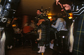 A GROUP OF PIPERS FROM THE LONACH PIPE BAND IN THE BAR OF THE COLQUHONNIE HOTEL AFTER THE LONACH HIGHLAND GATHERING AND GAMES, STRATHDON, ABERDEENSHIRE. PIC: P. TOMKINS/VisitScotland/SCOTTISH VIEWPOIN... 2004,TARTAN,PIPER,KILTS,KILT,INTERIOR,DRINKING,DRINK,BAGPIPES,ACCOMMODATION