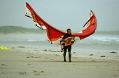 WILLIE ANGUS, A KITE AND WINDSURFING INSTRUCTOR ON THE BEACH AT CROSSAPOL, THE ISLE OF TIREE, INNER HEBRIDES.  PIC: P. TOMKINS/VisitScotland/SCOTTISH VIEWPOINT Tel: +44 (0) 131 622 7174   Fax: +44 (0)... 2004,WETSUIT,WATER,SPORTS,SANDY,SAND,KITESURFING,ISLAND,EXTREME,EQUIPMENT,ACTIVITY