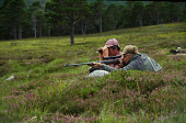 TWO MEN (ONE WITH BINOCULARS ONE WITH A GUN) LIE IN THE HEATHER WHILST OUT DEER STALKING ON THE MAR LODGE ESTATE TO BE FOUND ASTRIDE GLEN DEE ON THE SOUTHSIDE OF THE CAIRNGORM MOUNTAINS, ABERDEENSHIRE... SUMMER,ACTIVITY,PEOPLE,SPORT,HILL,SHOOTING,MOORS