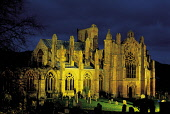 LOOKING ACROSS THE GRAVEYARD TO THE FLOODLIT MELROSE ABBEY (RUINS DATING FROM 1136 WHEN IT WAS FOUNDED BY DAVID I AND THE PLACE OF BURIAL OF ROBERT THE  BRUCE'S HEART) AT DUSK, IN THE CENTRE OF MELROS... ARCHITECTURE,RELIGION,HISTORIC SCOTLAND,HERITAGE,DRAMATIC,CEMETERY,BUILDING