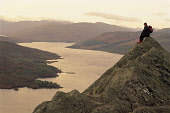 A HILL WALKER SITS PERCHED ON THE SUMMIT OF BEN A' AN WITH A VIEW OVER LOCH KATRINE BEHIND, THE TROSSACHS, STIRLINGSHIRE.PIC:PAUL TOMKINS/VisitScotland/SCOTTISH VIEWPOINTTel: +44 (0) 131 622 7174  Fax... ACTIVITY,WALKING,PEOPLE,MOUNTAIN,HILLWALKING,DRAMATIC,AUTUMN,ATMOSPHERIC