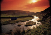 LOOKING ALONG THE LYNE WATER- A RIVER RISING IN THE PENTLAND HILLS AND RUNNING SOUTH TO THE RIVER TWEED, WHERE WALKERS HAVE SET UP THEIR TENT FOR THE NIGHT, IN ATMOSPHERIC LIGHT, SCOTTISH BORDERS. PIC... ACTIVITY,WATER,WALKING,FIELD,FARMING,DRAMATIC,AGRICULTURE