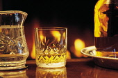 A STILL LIFE ARRANGEMENT OF A DRAM OF WHISKY IN A CUT CRYSTAL GLASS, WITH A LOG FIRE FLICKERING WARMLY BEHIND. PIC: VisitScotland/SCOTTISH VIEWPOINT Tel: +44 (0) 131 622 7174   Fax: +44 (0) 131 622 71... DRINK,WELCOMING,TRADITION,MALT,GENERIC