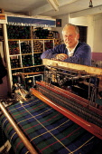 MURDO MACLEAN, A HARRIS TWEED WEAVER STANDS BY THE LOOM PRODUCING A TARTAN CLOTH AT THE TEXTILE MILL AT SWANIBOST (SUAINEBOST), ISLE OF LEWIS, WESTERN ISLES. PIC: P.TOMKINS/VisitScotland/SCOTTISH VIEW... CHARACTER,WOOL,TEXTILES,SMILE,PEOPLE,MACHINERY,ISLAND,INTERIOR,INDUSTRY,FACTORY