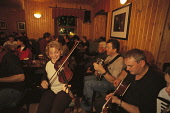 FOLK MUSICIANS SIT AROUND TABLES FOR AN IMPROMPTU SESSION OF MUSIC IN THE LOUNGE BAR- A PUB IN LERWICK (THE CHIEF TOWN OF THE ISLANDS), MAINLAND, SHETLAND. PIC: P.TOMKINS/VisitScotland/SCOTTISH VIEWPO... 2002,SMILE,SCOTLAND,MUSICAL,MUSIC,ISLAND,INTERIOR,INSTRUMENTS,FIDDLER,FIDDLE,DRINKS,DRINKING