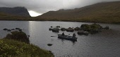 AN ANGLER FISHING FROM A ROWING BOAT ON LOCH BHOISIMID ( VOSHIMID) - ON THE AMHUINNSUIDHE CASTLE ESTATE, NORTH HARRIS, OUTER HEBRIDES  - M/R - AUTUMN