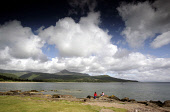 TWO CHILDREN SITTING ON ROCKS AT BRODICK BAY WITH A VIEW TOWARDS GOAT FELL (2867 FEET) ON THE ISLE OF ARRAN. PIC: P.TOMKINS/VisitScotland/SCOTTISH VIEWPOINT Tel: +44 (0) 131 622 7174   Fax: +44 (0) 13... COAST,WATER,SIT,SEA,SCOTLAND,ROCK,MOUNTAINOUS,MOUNTAIN,COASTAL