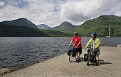 A COUPLE OF CYCLE TOURERS ON THE PIER  AT INVERSNAID, LOCH LOMOND, WITH A VIEW TO HILLS BEYOND. PIC: P.TOMKINS/VisitScotland/SCOTTISH VIEWPOINT Tel: +44 (0) 131 622 7174   Fax: +44 (0) 131 622 7175 E-... 2006,ACTIVITY,BICYCLE,BICYCLES,BIKE,BIKES,CYCLING,HILL,PANIERS,SUMMER,SUNNY,WATER