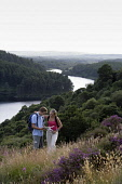 A COUPLE STUDY A MAP WHILST WALKING ABOVE LOCH TROOL - RUNNING SOUTH WEST THROUGH GLEN TROOL IN THE GALLOWAY FOREST PARK, DUMFRIES AND GALLOWAY. PIC: P.TOMKINS/VisitScotland/SCOTTISH VIEWPOINT Tel: +4... 2006,ACTIVITY,FORESTRY,ROMANTIC,SUMMER,TREES,WALKERS