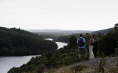 A COUPLE TAKE IN THE VIEW WHILST WALKING ABOVE LOCH TROOL - RUNNING SOUTH WEST THROUGH GLEN TROOL IN THE GALLOWAY FOREST PARK, DUMFRIES AND GALLOWAY. PIC: P.TOMKINS/VisitScotland/SCOTTISH VIEWPOINT Te... 2006,WALKERS,TREES,SUMMER,ROMANTIC,FORESTRY,ACTIVITY