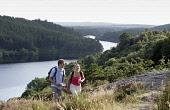 A COUPLE WALKING ABOVE LOCH TROOL - RUNNING SOUTH WEST THROUGH GLEN TROOL IN THE GALLOWAY FOREST PARK, DUMFRIES AND GALLOWAY. PIC: P.TOMKINS/VisitScotland/SCOTTISH VIEWPOINT Tel: +44 (0) 131 622 7174... 2006,ACTIVITY,FORESTRY,ROMANTIC,SUMMER,TREES,WALKERS