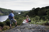A COUPLE TAKE IN THE VIEW WHILST WALKING ABOVE LOCH TROOL - RUNNING SOUTH WEST THROUGH GLEN TROOL IN THE GALLOWAY FOREST PARK, DUMFRIES AND GALLOWAY. PIC: P.TOMKINS/VisitScotland/SCOTTISH VIEWPOINT Te... 2006,ACTIVITY,FORESTRY,ROMANTIC,SUMMER,TREES,WALKERS