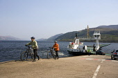 TWO CYCLISTS DISEMBARK FROM THE CORRAN FERRY AT ARDGOUR, LOCHABER DISTRICT, HIGHLAND. PIC: P.TOMKINS/VisitScotland/SCOTTISH VIEWPOINT Tel: +44 (0) 131 622 7174   Fax: +44 (0) 131 622 7175 E-Mail : inf... 2006,HIGHLANDS,WATER,VEHICLE,TRANSPORT,SUNNY,SPRING,SLIPWAY,MOUNTAINS,MOUNTAIN,LOCH LINNHE,JETTY,HILL,CYCLING,CYCLE TOURING,BIKES,BIKE,BICYCLES,BICYCLE,ACTIVITY