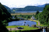 A YACHT SAILS THROUGH THE DUNARDRY LOCHS AT THE WESTERLY END OF THE CRINAN CANAL- BUILT BETWEEN 1793 &1801 WITH 15 LOCKS AND 9 MILES IN LENGTH IT CONNECTS LOCH FYNE WITH LOCH CRINAN ACROSS THE NORTH P... SUMMER,ACTIVITY,PEOPLE,BOAT,TRANSPORT,WATER,SUNNY