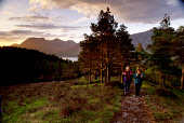 TWO HILL WALKERS MAKE THEIR WAY ALONG THE PATH THROUGH A FOREST TO BEN DAMPH (BEINN DAMH) IN ATMOSPHERIC LIGHT WITH THE MOUNTAINS OF TORRIDON VISIBLE BEHIND, NORTH WEST HIGHLANDS. PIC: VisitScotland/S... WATER,WALKING,COUPLE,MOUNTAIN,RUCKSACK,ACTIVITY,PEOPLE