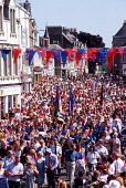A PROCESSION OF PEOPLE (INCLUDING A BRASS BAND) MAKE THEIR WAY THROUGH THE TOWN CENTRE OF SELKIRK AS PART OF THE COMMON RIDING CELEBRATIONS THAT HAVE TAKEN PLACE EVERY JUNE FOR FIVE CENTURIES, SELKIRK... SUMMER,SUNNY,PEOPLE,CROWD,BUNTING,FLAG,BANNER,EVENT