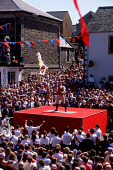 """CROWDS GATHER IN THE TOWN SQUARE TO WATCH THE """"CASTING OF THE COLOURS"""" CEREMONY- PART OF THE COMMON RIDING CELEBRATIONS THAT INVOLVES THE WAVING OF BANNERS TO SIGNIFY THE ONE SURVIVOR OF 79 TOWNSMEN T... SUMMER,PEOPLE,EVENT,STAGE,BUNTING,FLAG,BANNER"""