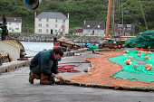 LOOKING OVER TO A FISHERMAN REPAIRING NETS ON THE HARBOUR AT MALLAIG- A BUSY FISHING PORT SITUATED AT THE ENTRANCE TO THE SOUND OF SLEAT AND LOCH INVER, HIGHLAND. PIC: S. GROSSET/SCOTTISH VIEWPOINT Te... BOATS,WATER,PEOPLE,INDUSTRY,COAST