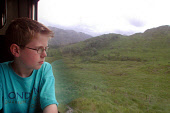 A YOUNG BOY TAKES IN THE VIEW FROM THE JACOBITE STEAM TRAIN AS IT JOURNEYS BETWEEN FORT WILLIAM AND MALLAIG, HIGHLAND. PIC: S. GROSSET/SCOTTISH VIEWPOINT Tel: +44 (0) 131 622 7174   Fax: +44 (0) 131 6... CHILD,TRANSPORT,SUMMER,PEOPLE,PASSENGER,MOUNTAIN