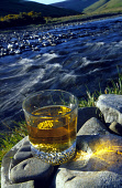 A GENERIC SHOT OF A GLASS OF WHISKY ON ROCKS BESIDE THE SIDE OF A RIVER.PIC: GLYN SATTERLEY/SCOTTISH VIEWPOINTTel: +44 (0) 131 622 7174  Fax: +44 (0) 131 622 7175E-Mail : info@scottishviewpoint.comThi... SCOTLAND,WATER OF LIFE,WATER,SUNNY,SUNLIGHT