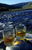 A GENERIC SHOT OF TWO OF GLASSES OF WHISKY ON ROCKS BESIDE THE SIDE OF A RIVER. PIC: GLYN SATTERLEY/SCOTTISH VIEWPOINT Tel: +44 (0) 131 622 7174   Fax: +44 (0) 131 622 7175 E-Mail : info@scottishviewp... GLASS,WATER OF LIFE,WATER,SUNNY,SUNLIGHT,SCOTLAND