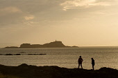 Two people silhouetted against the Firth of Forth with a view beyond to the Island of Fidra Island on a late summers evening, East Lothian.  Picture credit : Jason Baxter / Scottish Viewpoint This pho... Jason Baxter / Scottish Viewpoin 2013,coast,coastal,coastline,dusk,evening,pm,sea,seascape,seaside,serene,serenity,summer,atmospheric,silhouette,couple,island,islands,isle,isles,lighthouse,light,house