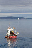 A small fishing boat heads out from Nairn into the Moray Firth, with an oil tanker in the distance, Moray. Ross Graham / SV 2013,summer,sunny,coast,coastal,coastline,water,sea,fisherman,fishermen,fishing,boat,boats,industry,industries