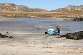 A fisherman with his dog by his small boat at low tide, Sorisdale Bay at the northern tip of the Island of Coll, Inner Hebrides. Ross Graham / SV 2013,spring,sunny,beach,beaches,sand,sandy,coast,coastal,coastline,water,sea,island,islands,isle,isles,argyll,pet,animal,fishing