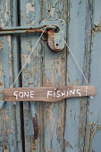 A detail of a hand painted sign stating Gone Fishing, on a cottage door. Scott Whitelaw / Scottish Viewpo 2013,summer,housing,house,door,front,entrance,message,signage,information,activity,activities,angling,fish
