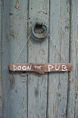A detail of a hand painted sign stating Doon the Pub, on a cottage door. Scott Whitelaw / Scottish Viewpo 2013,summer,housing,house,door,front,entrance,message,scots,drink,drinking,signage,information