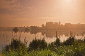 The view across a misty Linlithgow Loch to Linlithgow Palace and St Michael's Parish Church, Linlithgow, West Lothian. Dennis Barnes / Scottish Viewpoi 2013,autumn,atmospheric,silhouette,mist,fog,foggy,water,building,religion,attraction,visitor,tourist,history,heritage,historic,scotland,hs,path,footpath,walking
