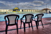 Three chairs by the side of the open air swimming pool at Stonehaven, Aberdeenshire. Bill McKenzie / Scottish Viewpoi 2013,summer,sunny,attraction,visitor,visitors,tourist,tourists,tourism,atmospheric,HDR,water,recreation,swim,swimmers,lido