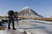 A photographer captures Stob Dearg, Buachaille Etive Mor, with a frozen River Coupall in the foreground, Highlands of Scotland. Andy Bennetts / Scottish Viewpoi 2010,winter,sunny,activity,activities,walk,walking,walker,walkers,people,person,photograph,tripod,ice,icey,icy,cold,snow,snowy,hobby,hobbies,munro,mountain,mountains,hill,hills