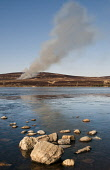 The view over a frozen Lochindorb to heather being burnt on a hillside, Highlands of Scotland. Mark Hicken / Scottish Viewpoint 2011,winter,sunny,sunshine,cold,ice,icy,water,smoke,plume,rock,rocks,moort,moorland,burn,burning