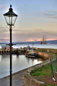 The harbour at Cromarty with a view beyond to oil rigs in the Cromarty Firth, Black Isle, Highlands of Scotland. Ross Graham / Scottish Viewpoint winter,atmospheric,atmosphere,fisherman,fishermen,fishing,boat,boats,trawler,trawlers,industry,industries,snow,snowy,lampost,lamppost,lamp,post,HDR