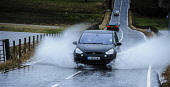 Cars negotiating a flooded road after the River Medwin burst its banks near Carnwarth, South Lanarkshire. Andrew Wilson / Scottish Viewpoi 2013,winter,weather,extreme,flood,flooding,flooded,wet,rain,raining,cloudy,water,spate,field,fields,countryside,car,spray,splash