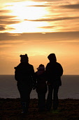 A family admire a winter sunset from the Brough of Birsay, off the coast of West Mainland, Orkney. Mark Ferguson / Scottish Viewpoi winter,sunset,dusk,Orkney,dramatic,Brough,Birsay,coast,coastal,coastline,water,sea,island,islands,isle,isles,west,mainland,atmospheric,atmosphere,child,children,kid,kids,family,families,silhouette,sil