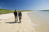 A couple walking on the beach near the Churchill Barrier No. 3 connecting Glimps Holm and Burray, Orkney. Picture Credit : Iain Sarjeant / Scottish Viewpoint  Tel: +44 (0) 131 622 7174  E-Mail : info@... 2012,summer,sunny,island,islands,isle,isles,people,person,beach,sand,sandy,white,romantic,activity,activities,walk,walking,walker,walkers,coast,coastal,coastline,water,sea