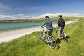 A couple cycling take in the view over Sands of Wright, South Ronaldsay, Orkney.Picture Credit : Iain Sarjeant / Scottish Viewpoint Tel: +44 (0) 131 622 7174 E-Mail : info@scottishviewpoint.com Web: w... 2012,summer,sunny,island,islands,isle,isles,activity,activities,cycling,cyclist,cyclists,bike,bikes,biking,biker,bikers,bicycle,bicycles,people,person,beach,sand,sandy,white,road