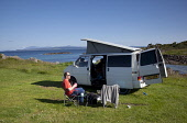 A man enjoys a drink by his campervan at the Portnadoran Caravan and Camping site, near Arisaig, Highlands of Scotland. Iain McLean / Scottish Viewpoint horizontal,day,summer,sunny,sunshine,blue,sky,skies,Arisaig,Lochaber,coast,coastal,coastline,water,sea,Portnadoran,campervan,caravanette,accommodation,touring,camping,campsite,camp,site,one,man,only,4